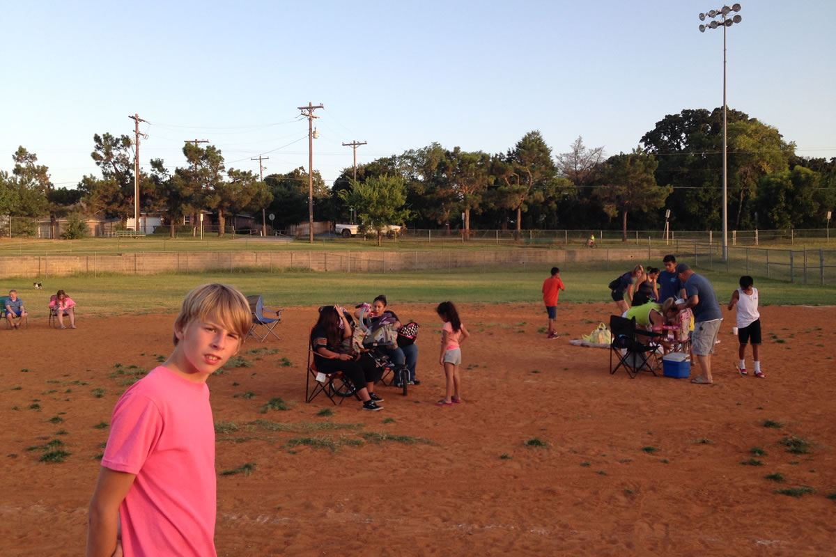 Boy Looks Toward Camera as Other Get Seated for Movies in the Park Event